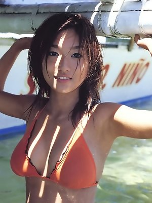 Beautiful asian girl having fun at the beach in a bikini
